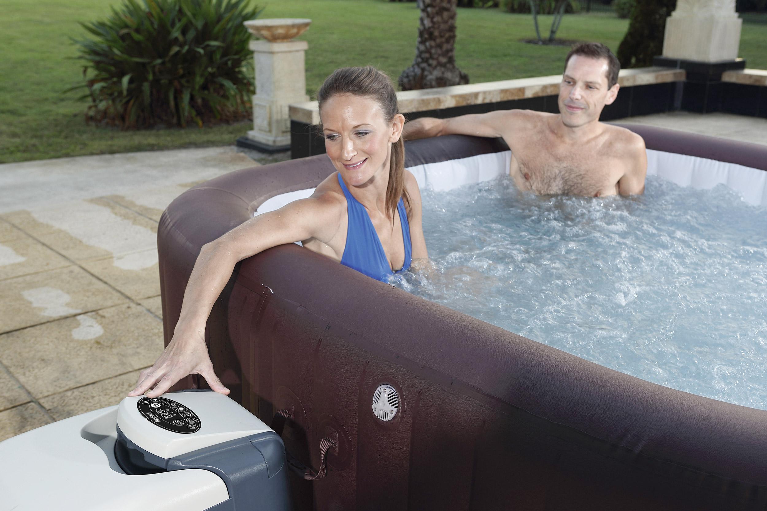 Paar badet im Whirlpool und benutzt das digitale Bedienfeld