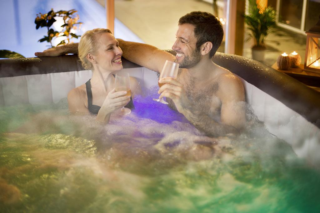 Paar badet in beleuchteten aufblasbaren Whirlpool