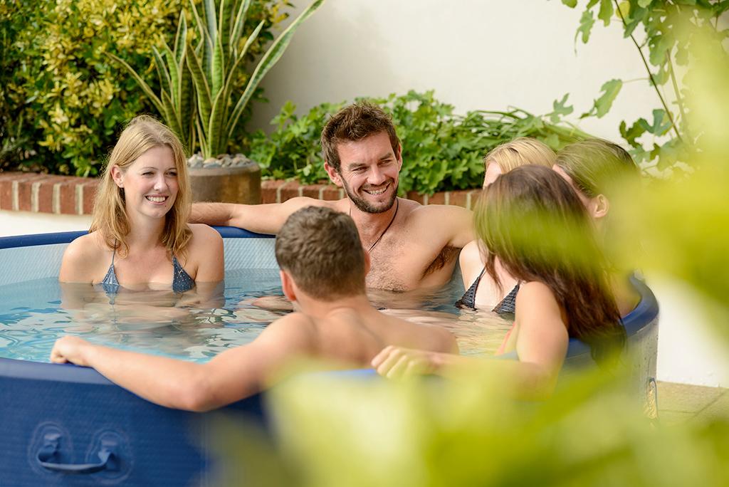 Familie von 6 Personen entspannt sich im Whirlpool im Garten
