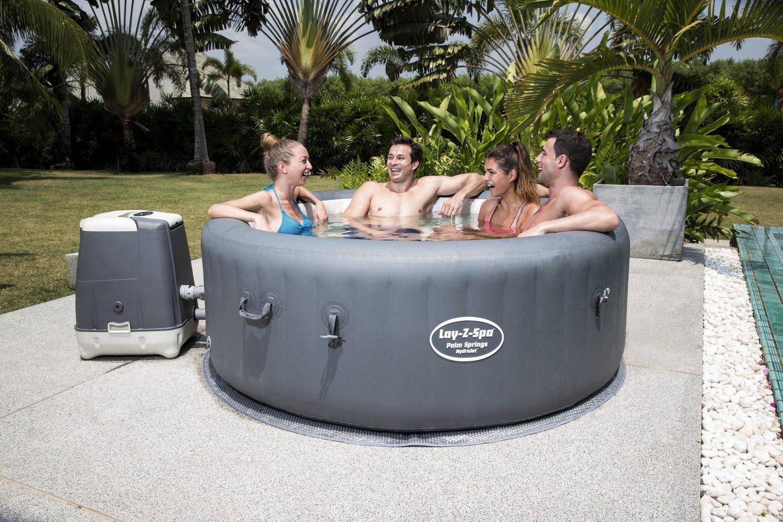 4 Freunde unterhalten sich im Whirlpool im Garten