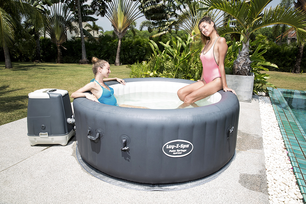 2 Mädchen erfrischen sich in einem aufblasbaren Whirlpool im Garten